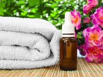 Floral spa and wellness design with oil bottle, towel stock photo