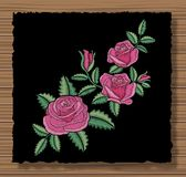 Floral stitched ornament with stitch flowers and sprigs. Embroidery roses and leaves on a dark flap cloth stock illustration
