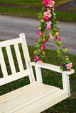 Floral Swing. Old outdoor white wooden swing decorated with colorful pink flowers on chain Royalty Free Stock Photos