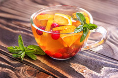 Floral tea with orange, cranberry, mint and ice. On an old wooden board Royalty Free Stock Photography