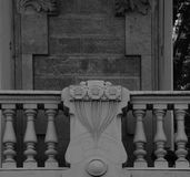 Floral trio between windows. Shot in black and white detail on the sculpture on the facade of this historic building representing some characters / animals / Stock Photography