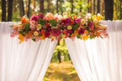 Floral wedding decorations. For beautiful romantic wedding ceremony outside at sunny forest. Horizontal color photography Royalty Free Stock Images