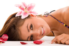 Floral Woman. Woman lying horizontally on her stomach, with her face turned toward the viewer. Model has a large pink lily in her hair Stock Image