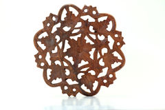 Floral Wood Carving. Round wood floral carving trivet from India; white background stock images