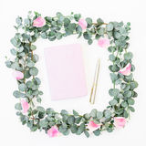 Floral wreath frame of pink petals and eucalyptus with notebook and pen on white background. Flat lay, top view. Floral wreath frame of pink petals and Stock Photos