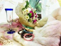 Florals on fur with Stone Jewelry. Lucky stone bracelets. Rutite quartz. Rhodochrosite. Tiger-eye. Ruby soyside. Azurite. Garnet Stock Image