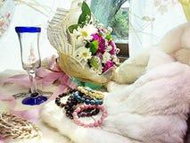 Florals and wine glass and stone jewelry on fur. Lucky stone bracelets. Rutite quartz. Rhodochrosite. Tiger-eye. Ruby soyside. Azurite. Garnet Royalty Free Stock Photo