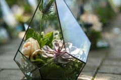 Florarium with fresh succulent and rose flowers. Event fresh flowers decoration. Florist workflow. Wedding banquet design stock photo