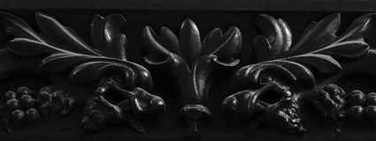Floreal dragons on the main wood door. Shot in black and white, detail on the sculpture on the facade of this historic building representing some animals. Set in Royalty Free Stock Photography