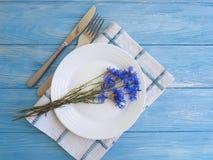 Florece el abastecimiento del menú de los acianos, placa, cuchillo de la bifurcación en un fondo de madera Fotos de archivo libres de regalías