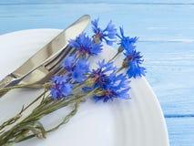 Florece el arreglo del abastecimiento del menú de los acianos, placa, cuchillo de la bifurcación en un fondo de madera Imagen de archivo libre de regalías