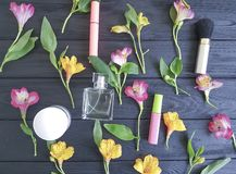 florece el modelo de madera negro poner crema del fondo del alstroemeria, cosméticos decorativos Foto de archivo libre de regalías
