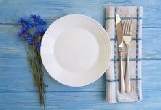 Florece el servicio del abastecimiento del menú de los acianos, placa, cuchillo de la bifurcación en un fondo de madera Fotos de archivo