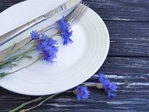 Florece el verano del arreglo del abastecimiento del menú de los acianos, placa, cuchillo de la bifurcación en un fondo de madera Imagenes de archivo