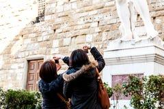 Florença, Itália - 13 de março de 2012: Turistas novos que tomam imagens da estátua perto das galerias de Uffizi fotos de stock royalty free