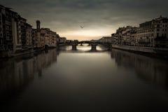 Florence Arno flod under en lynnig himmel på skymning Arkivbilder