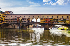 Florence city.View of Ponte Vecchio bridge in Italy. Close-up view of the bridge-old, Arno River in the foreground flowing under the arches Royalty Free Stock Photos