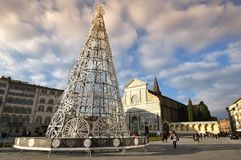 Florence, December 2018: Tourists and Christmas tree in the square of Santa Maria Novella with the Basilica on the background. royalty free stock photography
