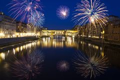 Florence with fireworks - Celebrating New Year in the city. Explosive fireworks around Ponte Vecchio on River Arno - Celebrating New year`s eve in Florence Royalty Free Stock Photo