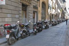 Florence gammal smal gata med parkerade sparkcyklar och mopeder royaltyfria foton