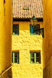 Florence inspired architecture yellow buildings. With green window frames in tight street Stock Photo
