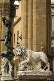 Florence, Italië - 23 April, 2018: een leeuwstandbeeld met Perseus met het Hoofd van Kwalstandbeeld achter het stock afbeeldingen