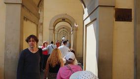 Florence, Italië, Juni, 2017: Een groep toeristen met een gids gaat langs de beroemde brug over Arno River in Florence stock footage