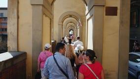 Florence, Italië, Juni, 2017: Een grote groep toeristen met een gids gaat binnen langs de beroemde brug over Arno River stock footage
