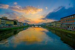 FLORENCE, ITALIË - JUNI 12, 2015: Het zonsonderganglicht maakt grote kleuren op Arno-rivier, Heilige Drievuldigheidsbrug bij de r Royalty-vrije Stock Foto
