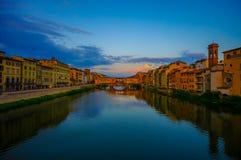 FLORENCE, ITALIË - JUNI 12, 2015: Zonsondergangfoto over Arno-rivier, Oude Brug en Vasari-gang aan het eind met grote hemel stock foto