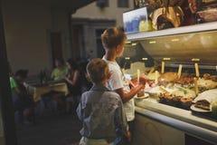 Florence, Italie 20 juillet 2014 Les garçons choisissent un grand choix de crème glacée ou de dessert dans le café dans un vitrai images libres de droits
