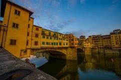 FLORENCE ITALIEN - JUNI 12, 2015: Den trevliga vattensikten med byggnader skuggar på Florence, gammal bro eller Ponte Vecchio Royaltyfri Foto