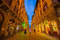 FLORENCE ITALIEN - JUNI 12, 2015: Oidentifierade turists som går på Florence på natten, shoppar är öppna med en innehavblått Arkivbilder