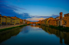 FLORENCE ITALIEN - JUNI 12, 2015: Solnedgångfoto över den Arno floden, gammal bro- och Vasari korridor på slutet med stor himmel Arkivfoto