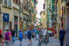 FLORENCE ITALIEN - JUNI 12, 2015: Turister och folket som korsar in i en comercial gata, lotter av, shoppar på sidorna A Fotografering för Bildbyråer
