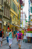FLORENCE ITALIEN - JUNI 12, 2015: Turister och folket som korsar in i en comercial gata, lotter av, shoppar på sidorna A Arkivfoton