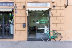 Florence ITALIEN September 10, 2016: Skyltfönstret av barberaren shoppar med barberarefrisören inom och cyklar parkerat nära shop Arkivbilder