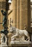 Florence, Italy - 23 April, 2018: a lion statue with the Perseus with the Head of Medusa statue behind it stock images