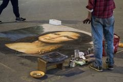 Florence, Italy - 23 April, 2018: a street artist draws a reproduction of Mona Lisa by Leonardo da Vinci on the ground stock image