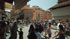 Tourists walking on famous Firenze landmark Ponte Vecchio bridge. Florence, Italy - August 1, 2019: Tourists walking on famous Firenze landmark Ponte Vecchio stock video footage