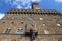 Florence Italy Historic clock tower building called Palazzo Vecc. Hio in the Signoria square with flags Stock Image