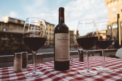 Closeup of bottle red wine Sant Alfonso Chianti Classico and glasses on table. Florence, Italy - June 24, 2018: Closeup of bottle red wine Sant Alfonso Chianti stock photography