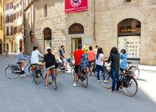 Florence. Florence, Italy - May 18, 2015: Tour by bicycle through the streets of Florence. A group of tourists cyclists on the Square of St. Trinita stock images