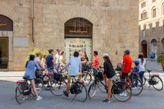 Florence. Florence, Italy - May 18, 2015: Tour by bicycle through the streets of Florence. A group of tourists cyclists on the Square of St. Trinita royalty free stock photography
