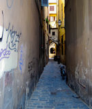 Florence Italy Alley with Bicycle and Graffiti. Setting sun casts amber glow to brick-paved alleyway. Lone bike and scooter litter are signs of local resident Stock Photo