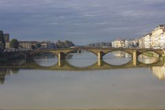 Carraia bridge in Florence on Arno river. FLORENCE, ITALY - NOVEMBER 25 2015: Frontal view of Carraia bridge in Florence on Arno river, with its reflection on Royalty Free Stock Photography