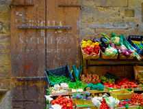 Vegetable Stand Florence Italy. The faded lettering on the wall and bright vegetables spilling over the street in this rustic alley of Florence, Italy stock images