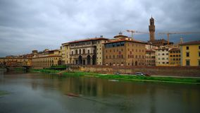 Time lapse of Uffizi Gallery and Palazzo Vecchio, Florence. Florence, October 2017: Time lapse of facade on the River Arno of the Uffizi Gallery. A crane is stock video footage