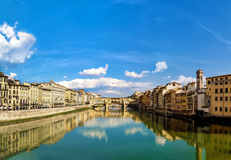 Florence and old bridge. Florence, with the blue sky reflected in the river Arno, creates a charming frame for the beautiful and historic old bridge Royalty Free Stock Images
