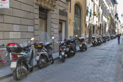 Florence old narrow street with parked scooters and motorbikes Royalty Free Stock Photos